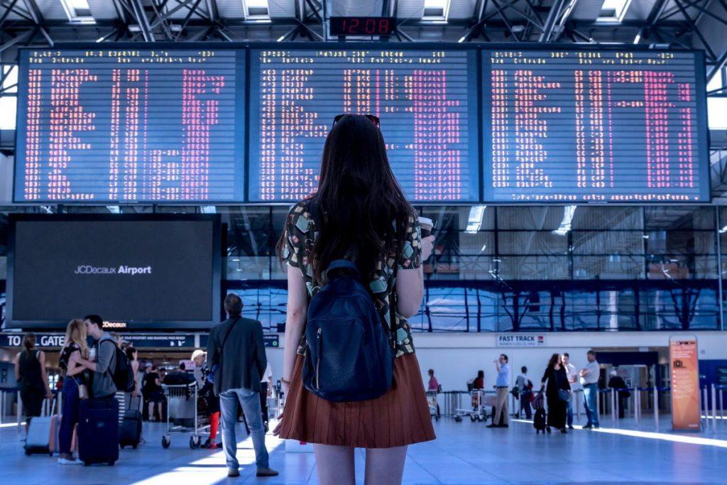 ragazza davanti tabellone aeroporto