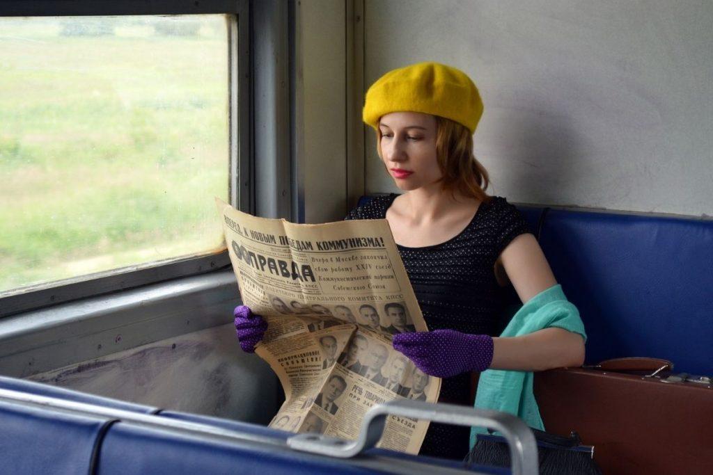 Galateo in treno ragazza con giornale seduta in treno